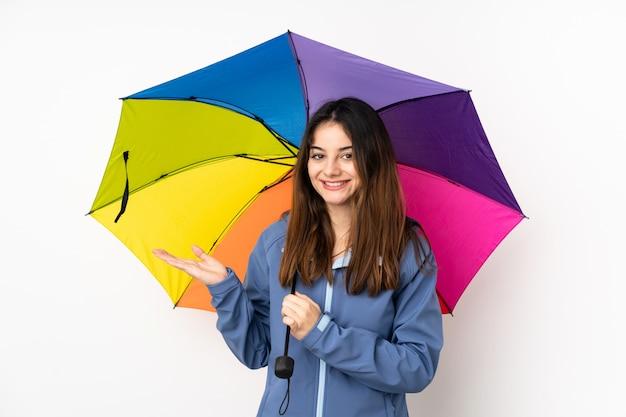 手のひらに想像上の空白を保持している白い壁に傘を保持している女性