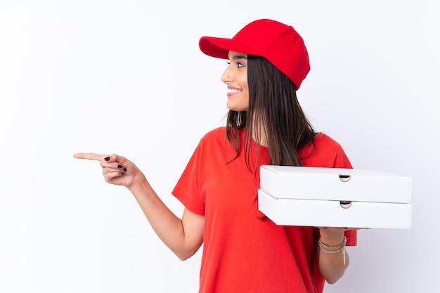 Женщина доставки пиццы держит пиццу над белой стеной, указывая в сторону, чтобы представить продукт