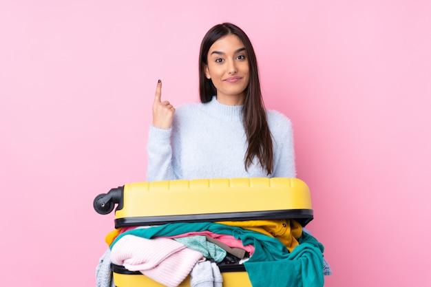 人差し指で素晴らしいアイデアを指している服でいっぱいのスーツケースを持つ旅行者の女性