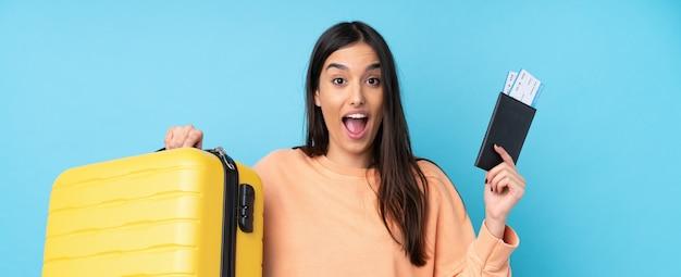 Молодая брюнетка женщина в отпуске с чемоданом и паспортом и удивлен