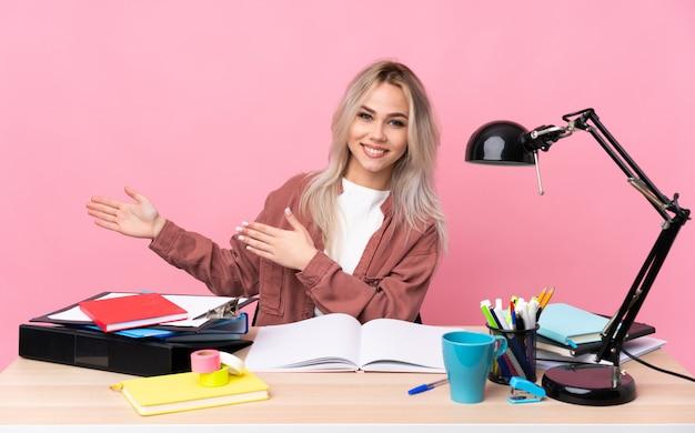 Молодой студент женщина, работающая в таблице, протягивая руки в сторону за приглашение прийти