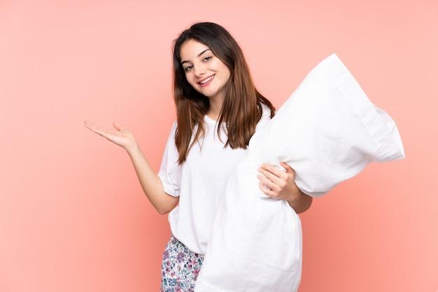 ピンクの壁にパジャマ姿の若い女性が手を差し伸べるために側に手を伸ばす