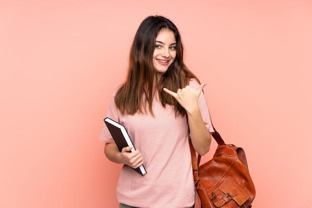 Молодой студент женщина собирается в университет над розовой стеной, крича с широко открытым ртом