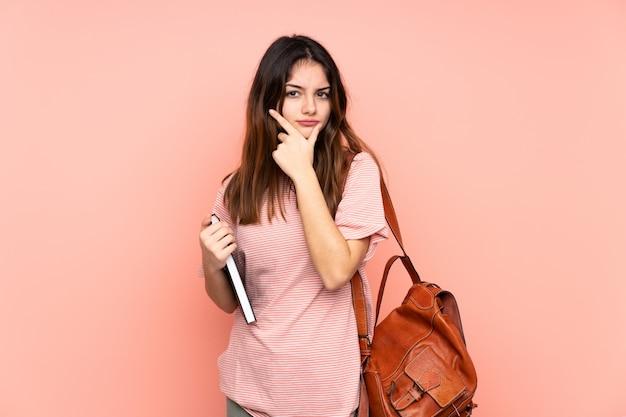 アイデアを考えてピンクの壁を越えて大学に行く若い学生女性