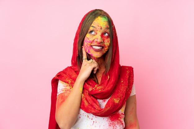 見上げながらアイデアを考えてピンクの壁に彼女の顔にカラフルなホーリーパウダーを持つ若いインド人女性