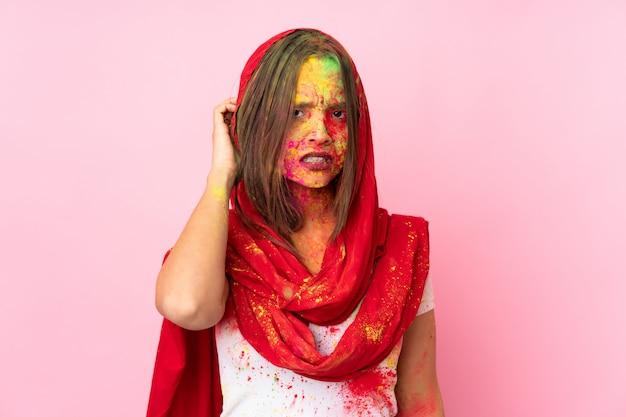 疑問を持つピンクの壁に彼女の顔にカラフルなホーリーパウダーを持つ若いインド人女性