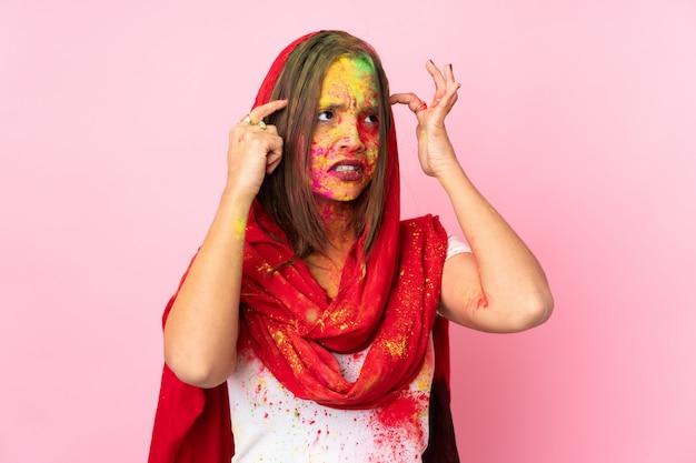 ピンクの壁に疑問や思考を持つ彼女の顔にカラフルなホーリーパウダーを持つ若いインド人女性