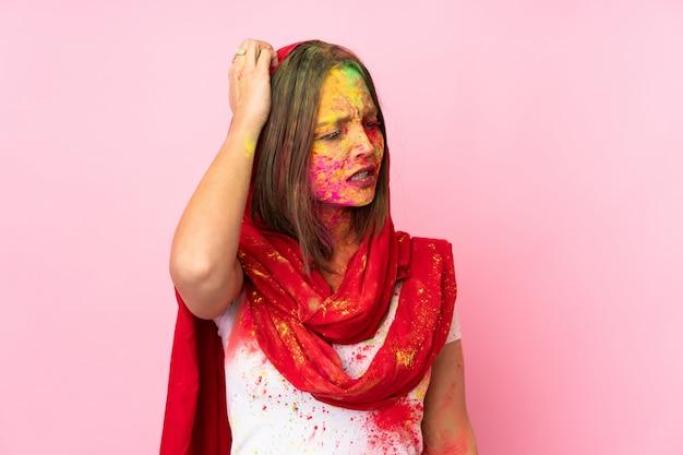 頭をかきながら疑問を持つピンクの壁に彼女の顔にカラフルなホーリーパウダーを持つ若いインド人女性