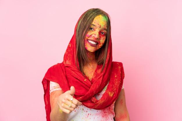 Молодая индийская женщина с красочными порошками холи на лице на розовой стене с большими пальцами вверх, потому что случилось что-то хорошее