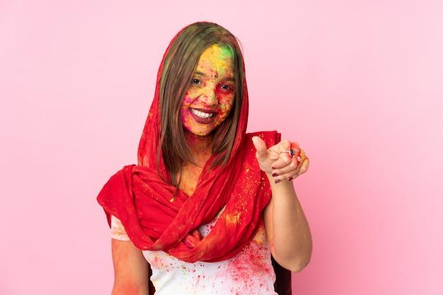 Молодая индийская женщина с красочными порошки холи на ее лице на розовой стене, давая пальцы вверх жест