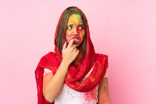 ピンクの壁に緊張と怖がって彼女の顔にカラフルなホーリーパウダーを持つ若いインド人女性