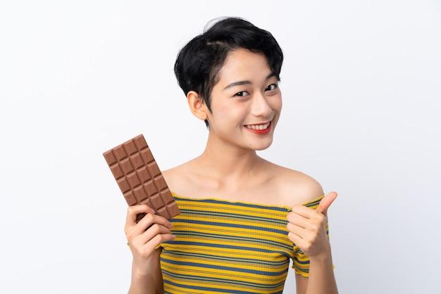 Молодая азиатская женщина принимая таблетку шоколада и с большим пальцем руки вверх