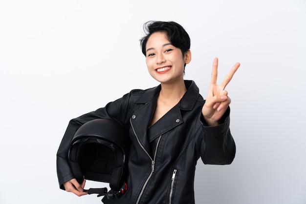 Молодая азиатская женщина с шлемом мотоцикла усмехаясь и показывая знак победы