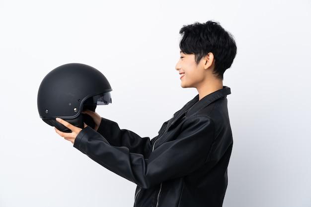 Молодая азиатская женщина с мотоциклетным шлемом с счастливым выражением