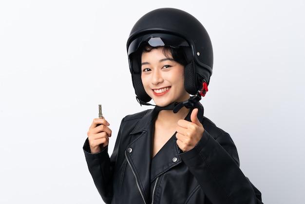オートバイのヘルメットとキーを持つ若いアジア女性