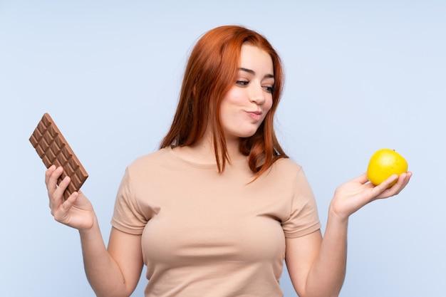 赤毛のティーンエイジャーの女性の片方の手でチョコレートタブレットと他の手でリンゴを取りながら疑問を持っています。