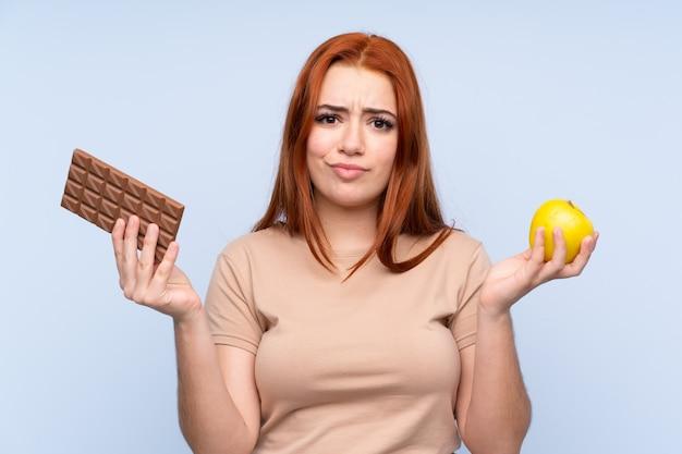 Рыжая девушка-подросток с сомнением берёт шоколадную таблетку в одной руке и яблоко в другой