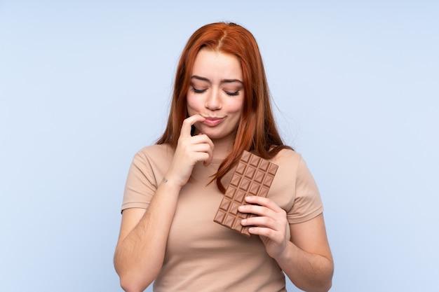 赤毛のティーンエイジャーの女性がチョコレートタブレットを服用し、疑問を持っています。