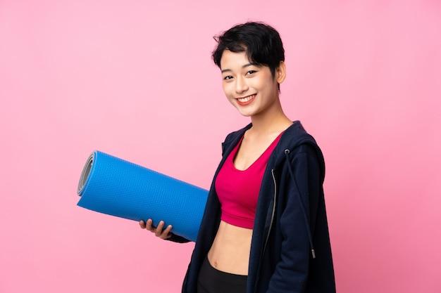 Молодая спортивная азиатская женщина с ковриком