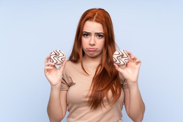 Рыжий подросток женщина, держащая пончики с грустным выражением