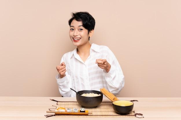 麺と寿司のボウルを持つテーブルで若いアジア女性があなたに指を指す