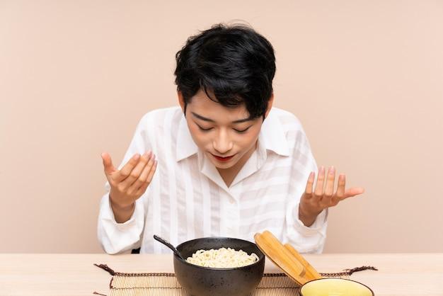 Молодая азиатская женщина в таблице с миской лапши и суши