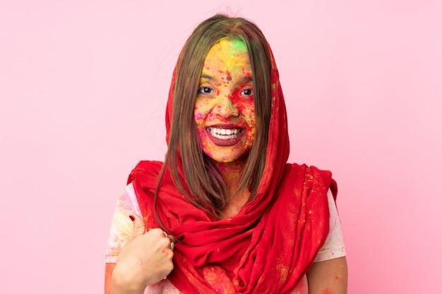 Молодая индийская женщина с красочными порошками холи на ее лице на розовой стене с удивленным выражением лица