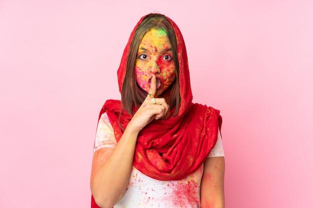 口に指を入れて沈黙ジェスチャーの兆候を示すピンクの壁に彼女の顔にカラフルなホーリーパウダーを持つ若いインド人女性