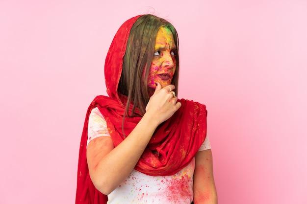 疑問を持つピンクの壁に彼女の顔にカラフルなホーリーパウダーと混乱している表情を持つ若いインド人女性