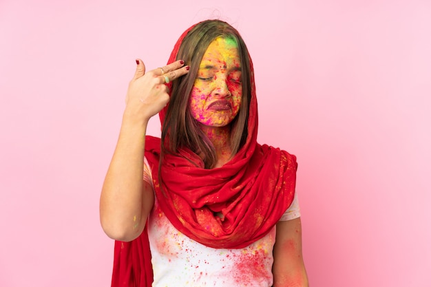 Молодая индийская женщина с красочными порошками холи на лице на розовой стене с проблемами, делая жест самоубийства