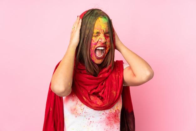 ピンクの壁に彼女の顔にカラフルなホーリーパウダーを持つ若いインド人女性が圧倒されると強調