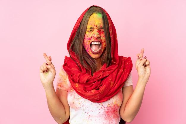 Молодая индийская женщина с красочными порошками холи на ее лице на розовой стене с пересечением пальцев