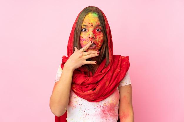 ピンクの壁に驚いたとショックを受けた彼女の顔にカラフルなホーリーパウダーを持つ若いインド人女性