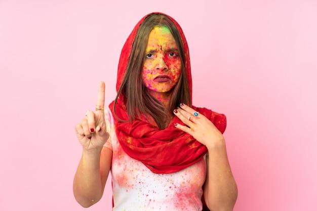 Молодая индийская женщина с красочными порошками холи на лице на розовой стене, считая один с серьезным выражением