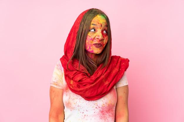 見上げながら疑問を持つピンクの壁に彼女の顔にカラフルなホーリーパウダーを持つ若いインド人女性