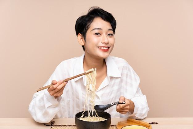 麺のボウルとテーブルの若いアジア女性