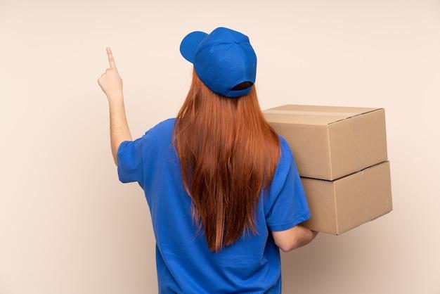 Молодая женщина доставки подростка, указывая назад указательным пальцем
