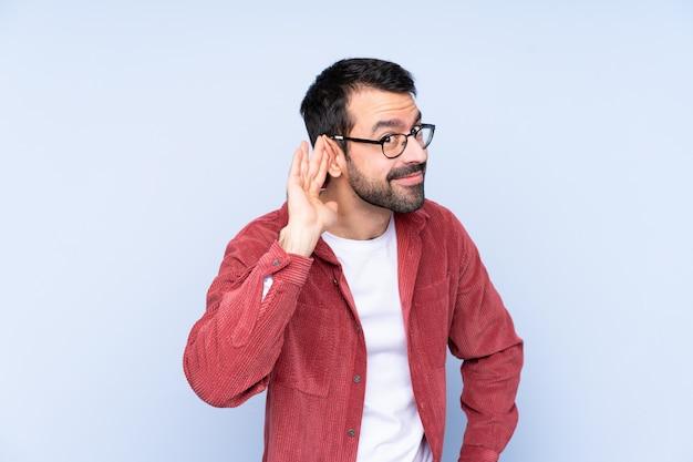 耳に手を置くことで何かを聞いてコーデュロイジャケットを着ている若い男