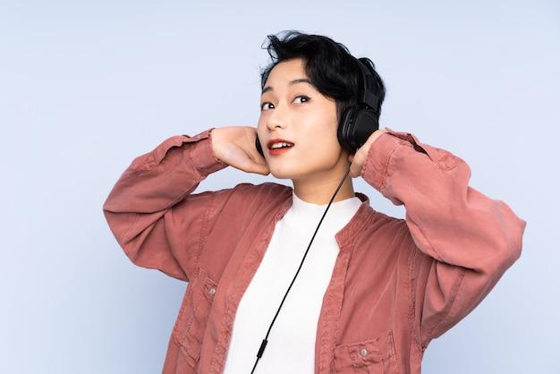 Молодая азиатская женщина слушая к музыке