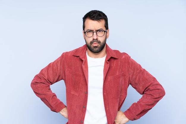 Молодой человек, одетый в вельветовый пиджак злой
