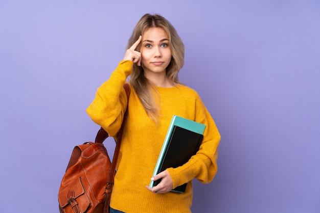 Девушка студента подростка на фиолетовой стене думая идея