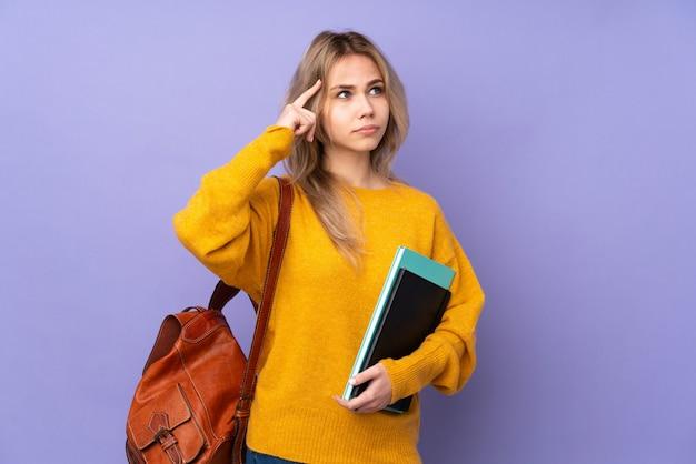 Девушка студента подростка на фиолетовой стене имея сомнения и думая