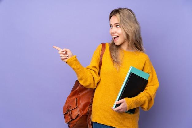 Девушка студента подростка на фиолетовой стене указывая палец в сторону