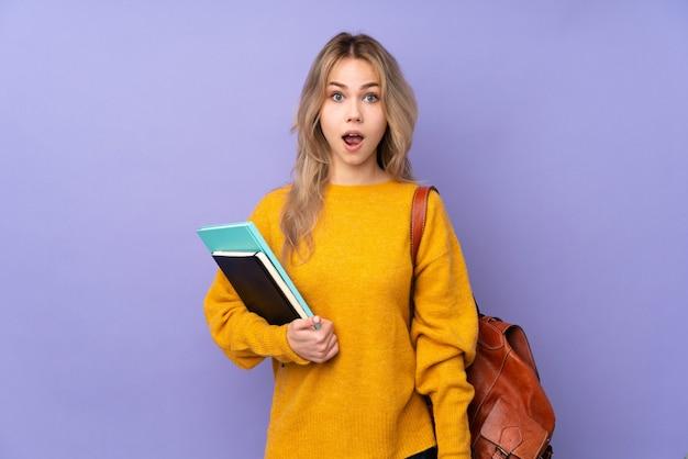 Девушка студента подростка на фиолетовой стене с выражением лица сюрприза