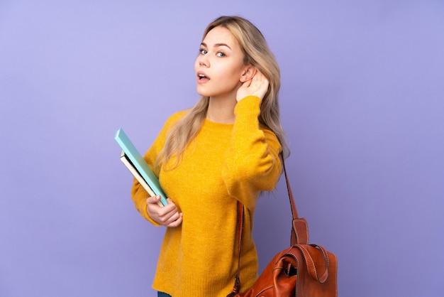 Девушка студента подростка на фиолетовой стене слушая к что-то, кладя руку на ухо