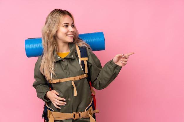 側に指を指しているピンクの壁に大きなバックパックを持つティーンエイジャー登山少女