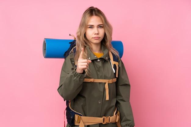 ピンクの壁に大きなバックパックでティーンエイジャーの登山家の女の子がイライラし、前方を向く