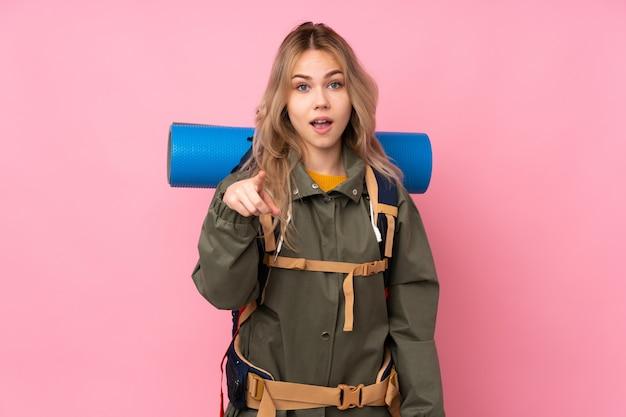 ピンクの壁に大きなバックパックとティーンエイジャーの登山家の女の子を驚かせたとフロントを指す