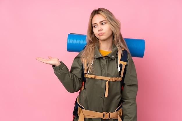 疑問を持つ空白を保持しているピンクの壁に大きなバックパックとティーンエイジャーの登山家の女の子