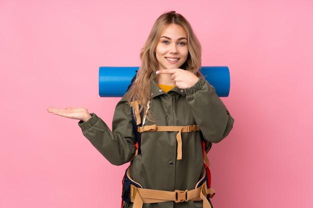 手のひらに想像上の空白スペースを保持しているピンクの壁に大きなバックパックとティーンエイジャーの登山家の女の子